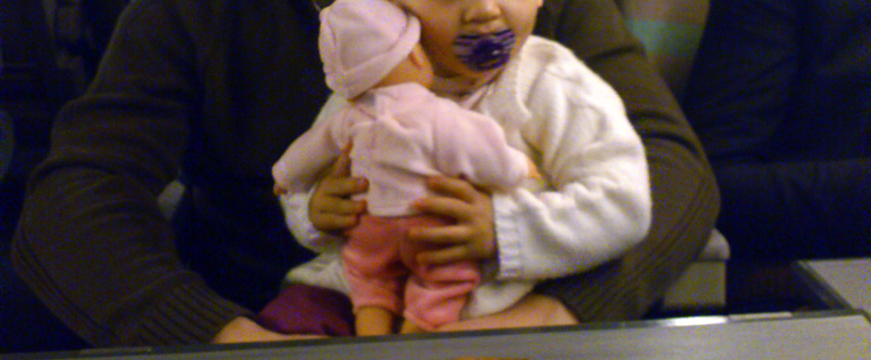 Loulou dans les bras de papa qui porte sa poupée